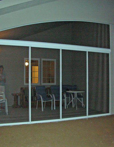 """This is the patio we did in Oregon City at a retirement center. The top is done in Screen-eze and the bottom is done in sliding patio door panels. I added a 3"""" aluminum I-beam over the doors for support and to attach the u-channels to plus 4 tracks on the bottom to roll the doors on."""