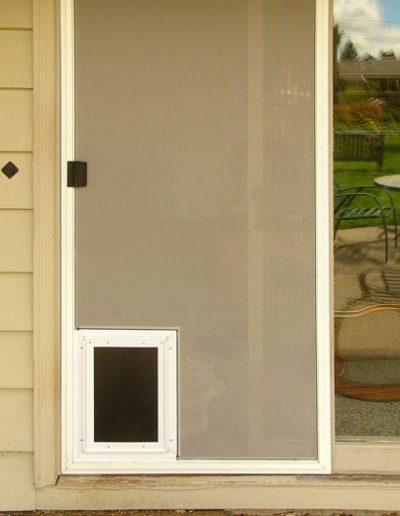 This heavy duty patio screen door has gray pet mesh a rubber flap dog door in it.