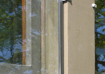 This storm window panel is inset into the trim of the window and held on with off-set clips.
