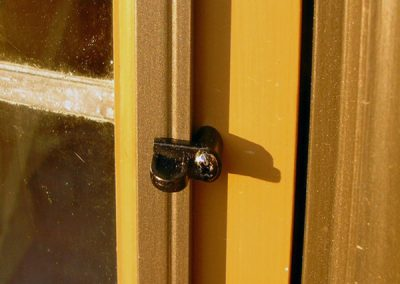This storm window panel is surface mounted and held on by a pivoting turn clip.