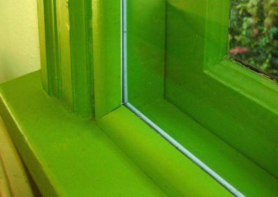 This panel is inset into the trim of the window, inside the home and covered with green quarter round to conceal the storm window frame.