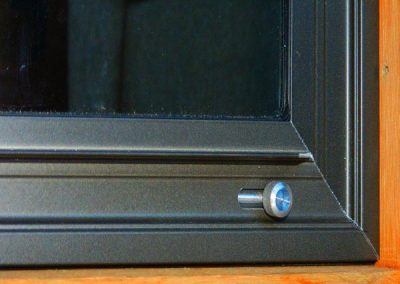 This storm window panel is inset into the trim of the window and held on with off-set clips